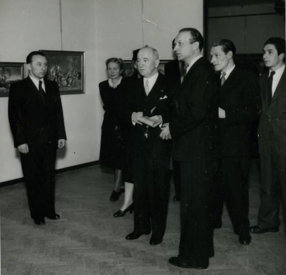 Fotografie zachycující návštěvu prezidenta Edvarda Beneše v Pražském salonu Vladimíra Žikeše v roce 1945 (Žikeš je přihlížející muž úplně vlevo snímku)
