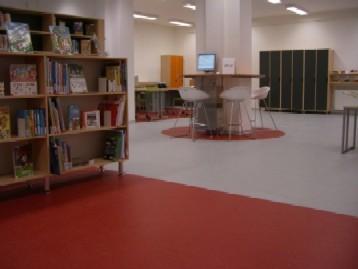 Pohled z dětského oddělení v nové části budovy do staré (v pozadí vlevo budoucí počítačová studovna; šatní skříňky se nacházejí vlevo od vstupu do knihovny)