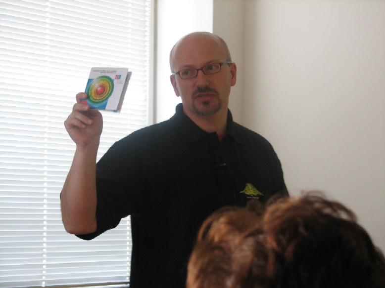 Hanuš Hemola ukazuje brožurku, v níž je vysvětlena nová koncepce služeb Národní knihovny ČR