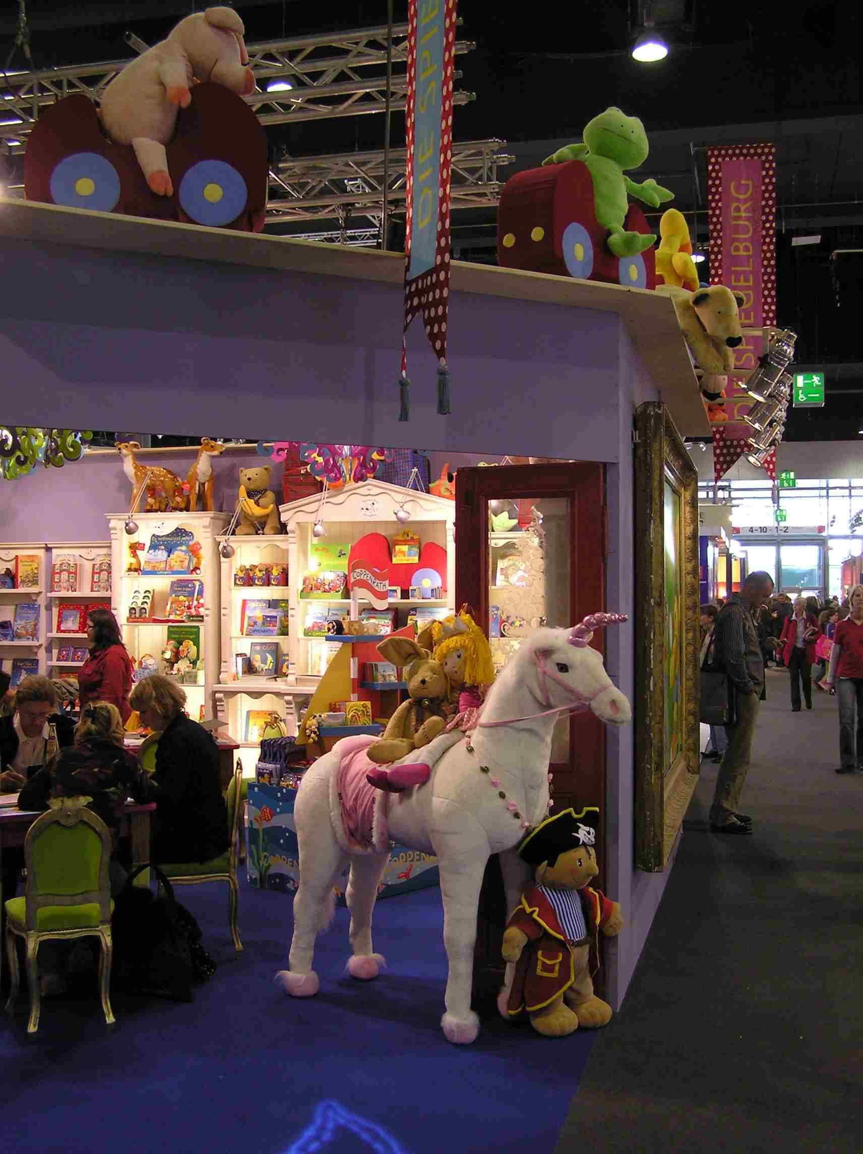 Obr. 1: Frankfurtský knižní veletrh letos navštívilo, asi i kvůli páteční stávce železničářů, o něco méně návštěvníků než loni, ale lidí tam bylo i tak dost (dohromady prý 283 293).  Způsoby, kterými se všech 7 448 vystavovatelů snažilo přilákat návštěvníky, byly nejrůznější:  oblíbeným prostředkem jsou například maskoti: v tomto stánku bylo zvířat možná více než knih, bájný jednorožec sloužil jako průvodce do zcela jiného, pohádkového světa.