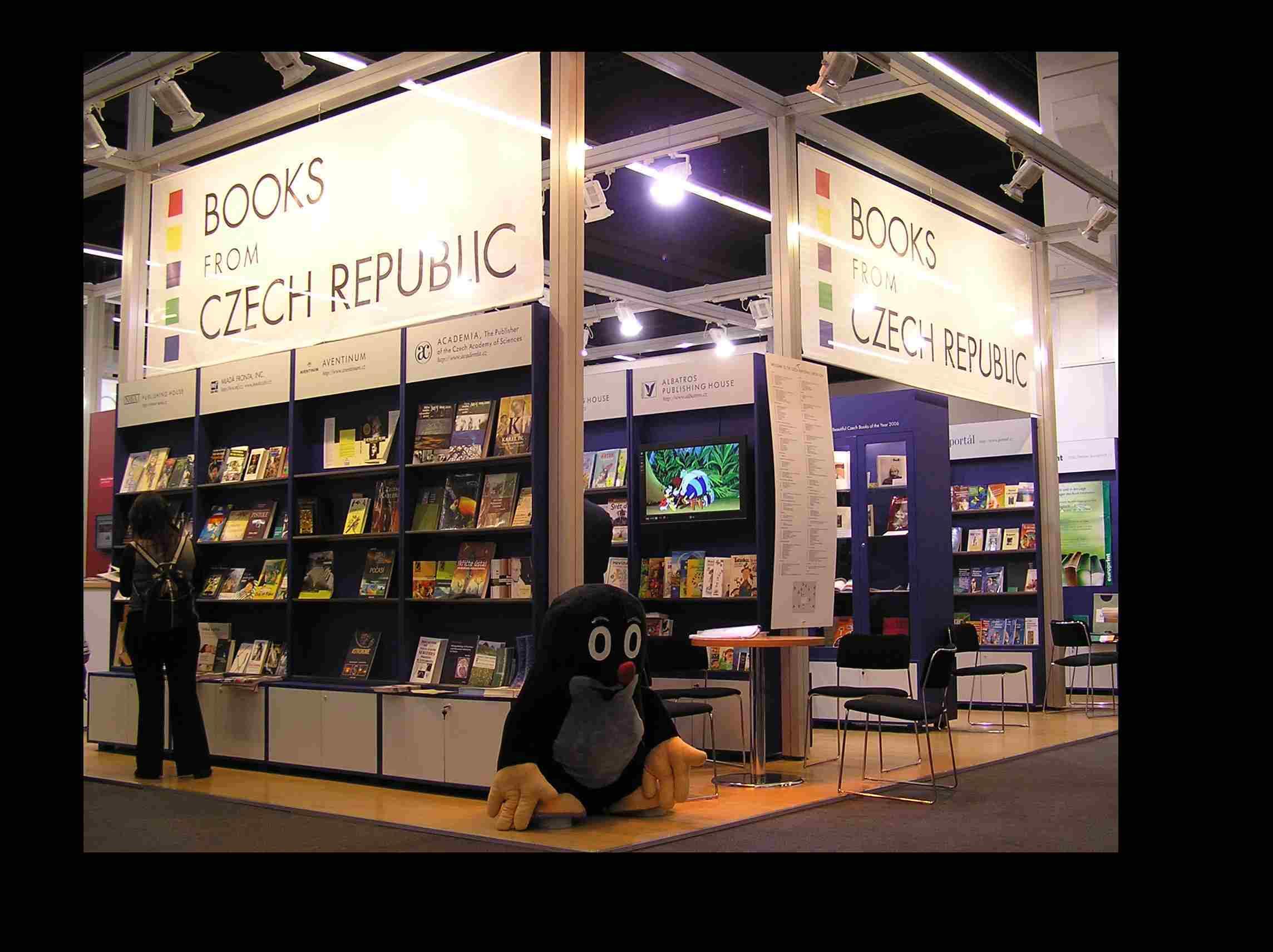 """Obr. 3: Jak jsem se dozvěděl ze Světa knihy, krtek byl součástí prezentace nakladatelství Albatros, ale návštěvníky byl podle mne spojován s naším stánkem obecně. Reakce prý byly časté a veskrze pozitivní (vlastní fotografii s krtečkem si z veletrhu odnášelo dost lidí), což je důkazem toho, že krteček je v Německu relativně dobře známý a populární. Na Wikipedii se sice jako perzonifikace České republiky uvádí Jára Cimrman, ten by ale většině Němců nic neřekl, zato krteček jako český maskot zafungoval docela dobře. Vždyť měl v Německu dokonce i vlastní internetové stránky, které byly zřejmě tak úspěšné, že musely být na nátlak držitelů autorských práv staženy. Krteček nechal na stránkách pouze vzkaz: """"jsem v Praze"""" a jeho krátký pobyt ve Frankfurtu mohli Němci chápat jako určitou, i když nedostatečnou, satisfakci."""