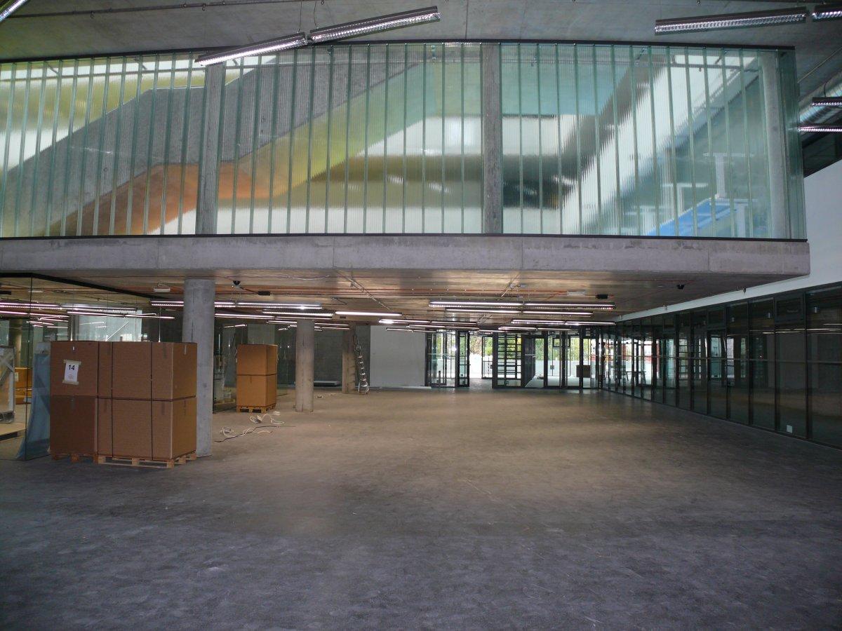 Centrální komunikace knihovny se zavěšeným vlašťovčím hnízdem haly služeb. (na paletách je v krabicích složena automatická třidička knih využívající technologie RFID)