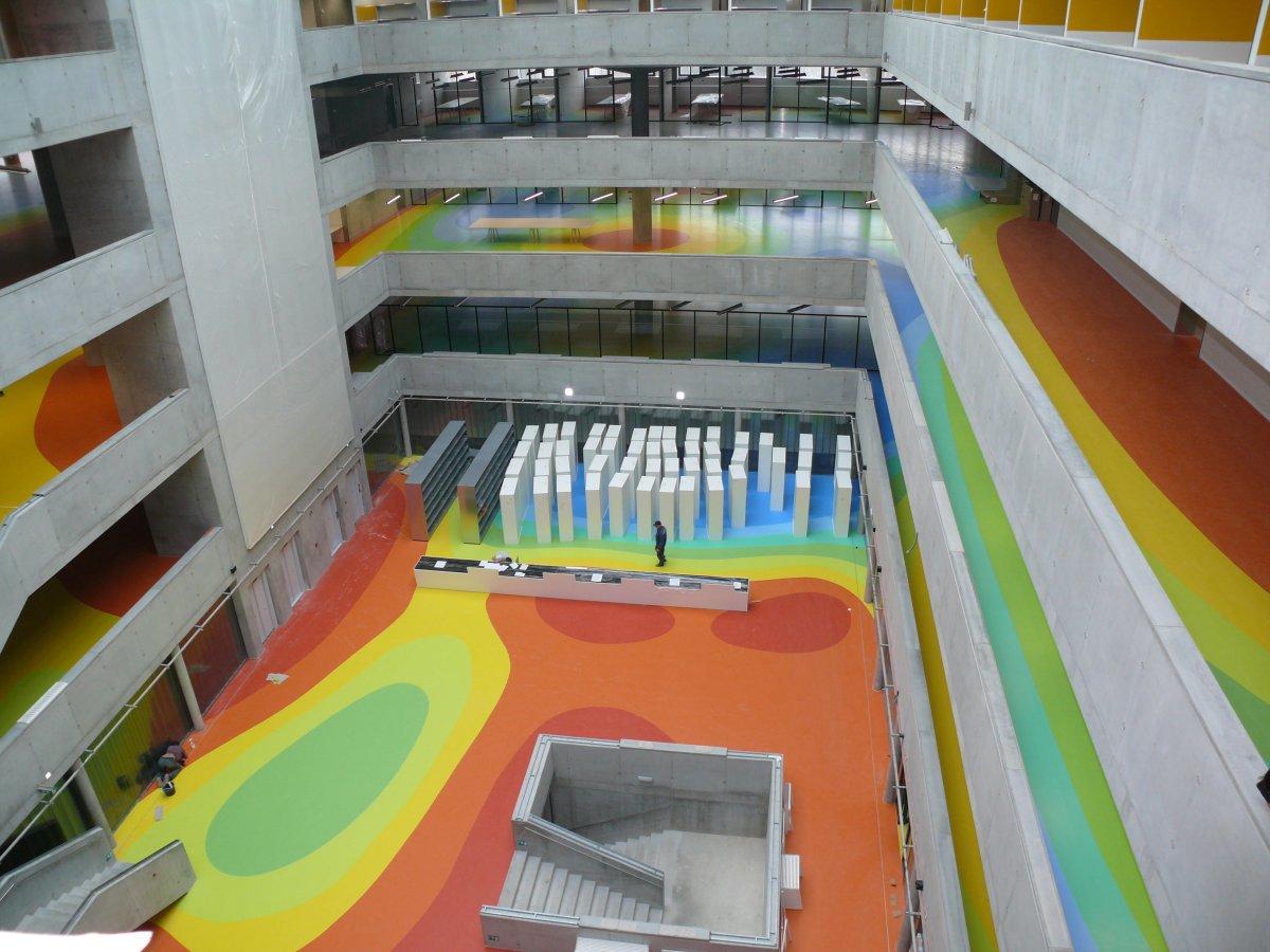 Pohled do jádra knihovny na výpůjční pult; barevné obrazce na podlaze vyjadřují úrovně napětí v předpjatém betonu