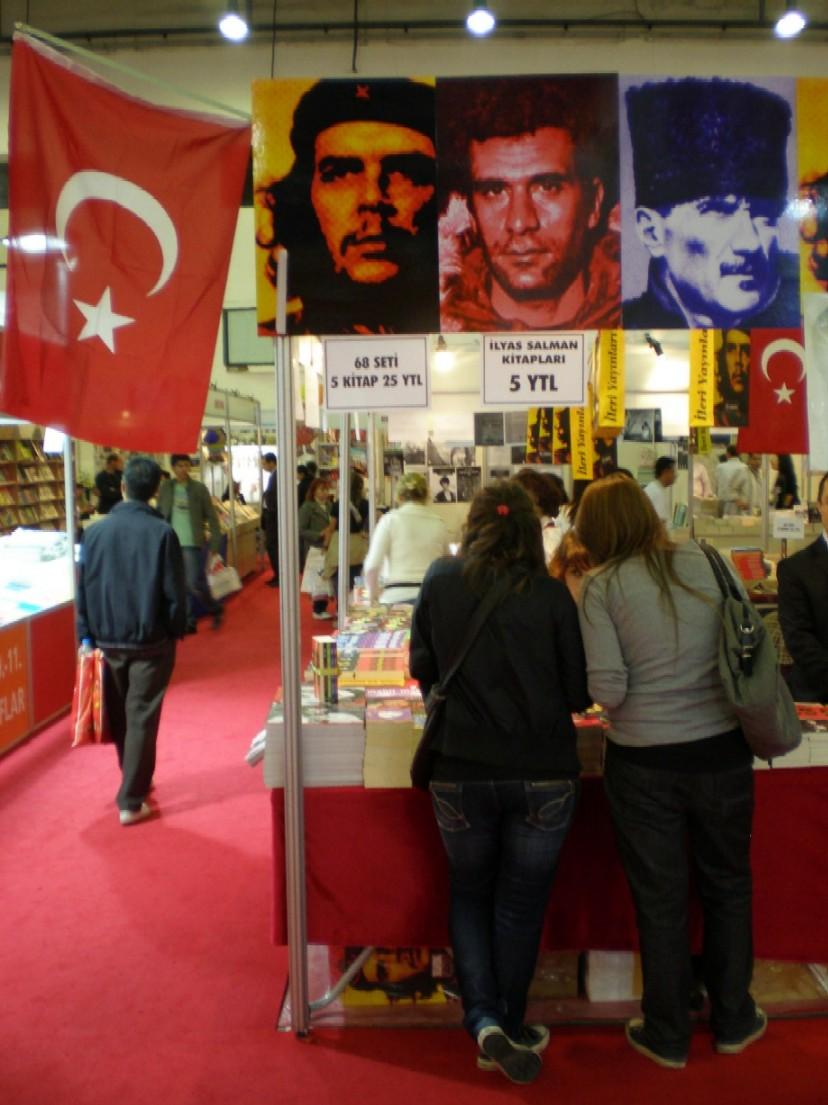 """Obr. 3 a 4: Na veletrhu se ovšem na Atatürka odvolával opravdu leckdo - nejen Atatürkovo výzkumné středisko se svými Příručkami kemalistického myšlení a spoustou dalších knih od Atatürka i o něm (kde by člověk jeho portrét chápal), nejen u mnoha dalších spíše pravicově a nacionalisticky orientovaných organizací. Jeho portrét visel i na místech, kde se prezentovala nakladatelství a organizace orientované přesně opačně, levicově. Atatürk se tak objevoval vedle portrétu Che Guevary a přední osobnosti tureckého studentského hnutí v roce 1968 Denize Gezmişe (1947-1972) jako významný turecký revolucionář, pod jehož vedením byla 12. června 1968 studenty obsazena istanbulská univerzita - právě rok 1968 v Turecku byl letos jedním z hlavních témat istanbulského veletrhu. Nutno podotknout, že označení Atatürka za revolucionáře není neodůvodněné: epochální proměna, kterou Turecko pod jeho vládou prošlo, byla skutečně revoluční (ovšem bez miliónů mrtvých jako v Rusku), jedním z hlavních principů """"kemalismu"""" také ne náhodou bylo """"revolucionářství"""" (chápané ovšem v naší terminologii jako """"reformismus"""" a zásada odmítnutí návratu do osmanských dob), ve dvacátých letech navíc Atatürk hledal hlavního spojence Turecka právě v Sovětském svazu. To mu prý nicméně nevadilo, aby roku 1929 neposkytl azyl Trockému."""