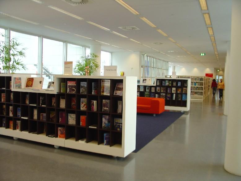 Openbare Bibliotheek Den Haag – regály s učebnicemi, vzadu pohovka