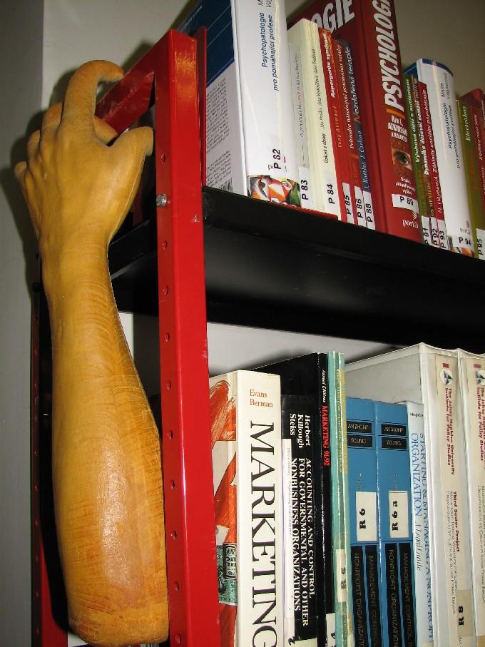 Pomocná ruka (symbol společnosti) šplhající po regálu s knihami
