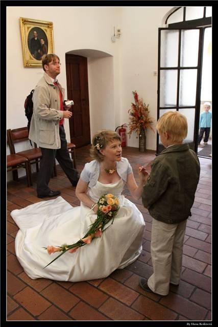 Nevěsta přijímá tajný vzkaz od Vojtáška juniora. Zpovzdálí přihlíží též Štogr junior.