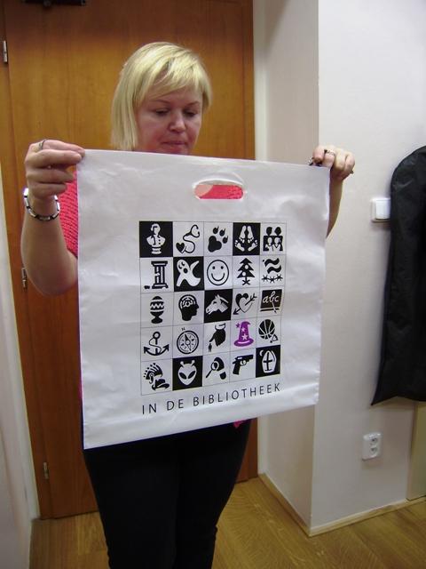 Mgr. Dagmar Bahnerová, ředitelka Městské knihovny Louny, ukazující grafické symboly užívané v knihovně nizozemského partnerského města Barendrecht