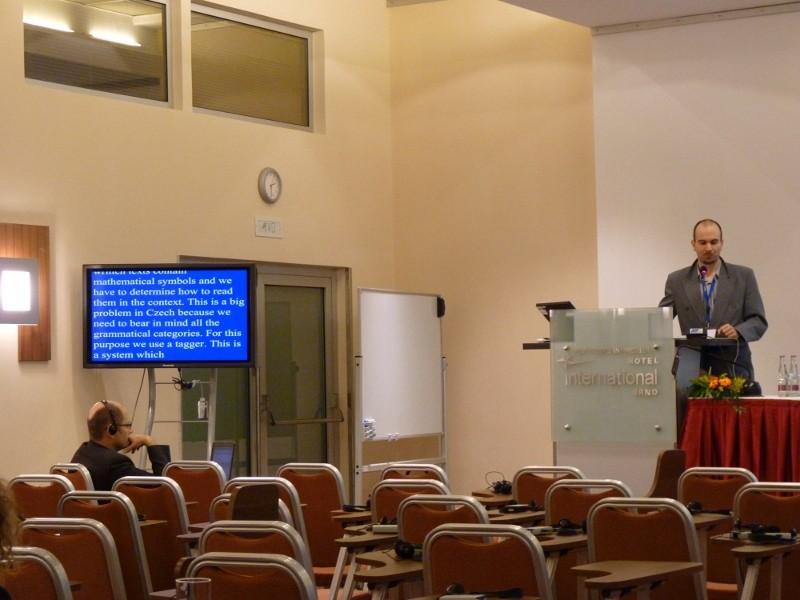 Zdeněk Hanzlíček. Vlevo lze spatřit obrazovku s překladem jeho přednášky do angličtiny