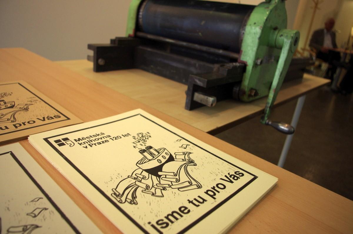 Historický lis a plakáty se symbolem výročí knihovny
