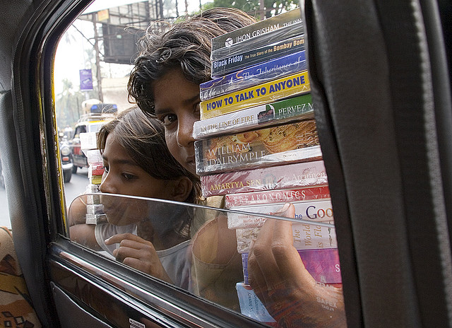 Děti na ulicích Mumbaje se snaží prodat knihy lidem vautech a taxíkách. Západní turisté jsou skutečným magnetem
