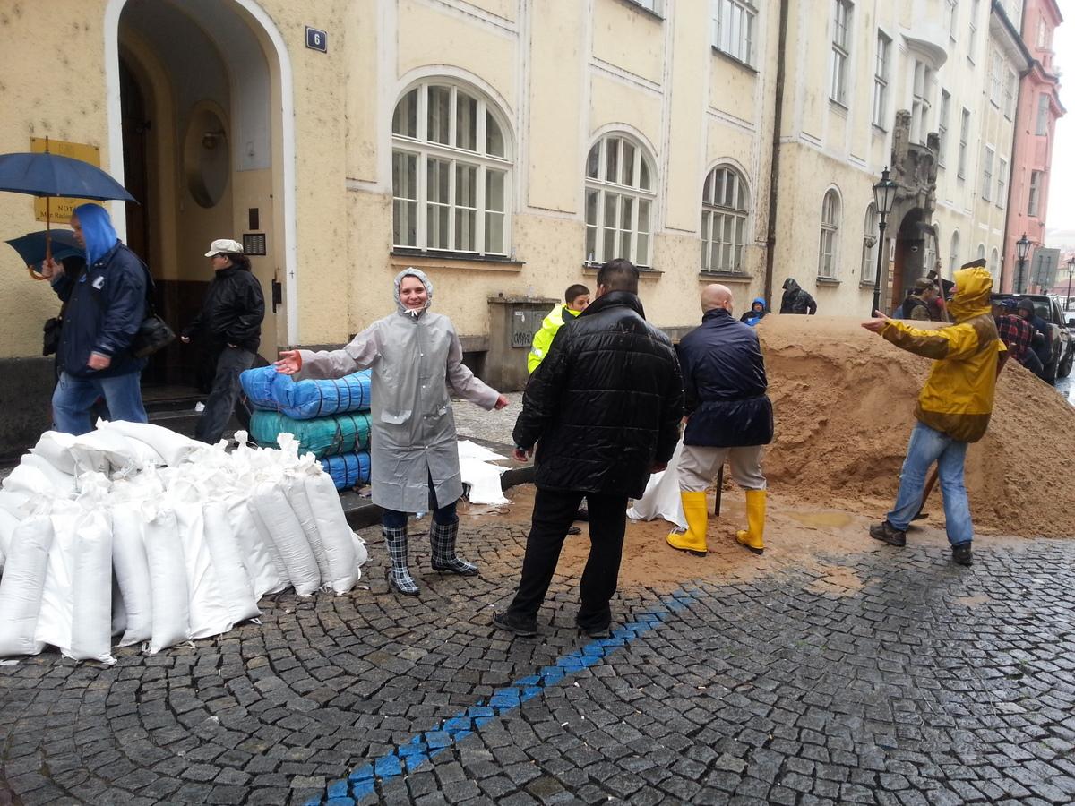 Zaměstnanci NK a dobrovolníci při plnění pytlů s pískem