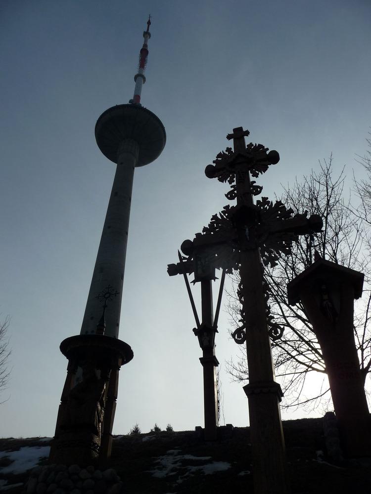 Vyřezávané dřevěné kříže a televizní věž