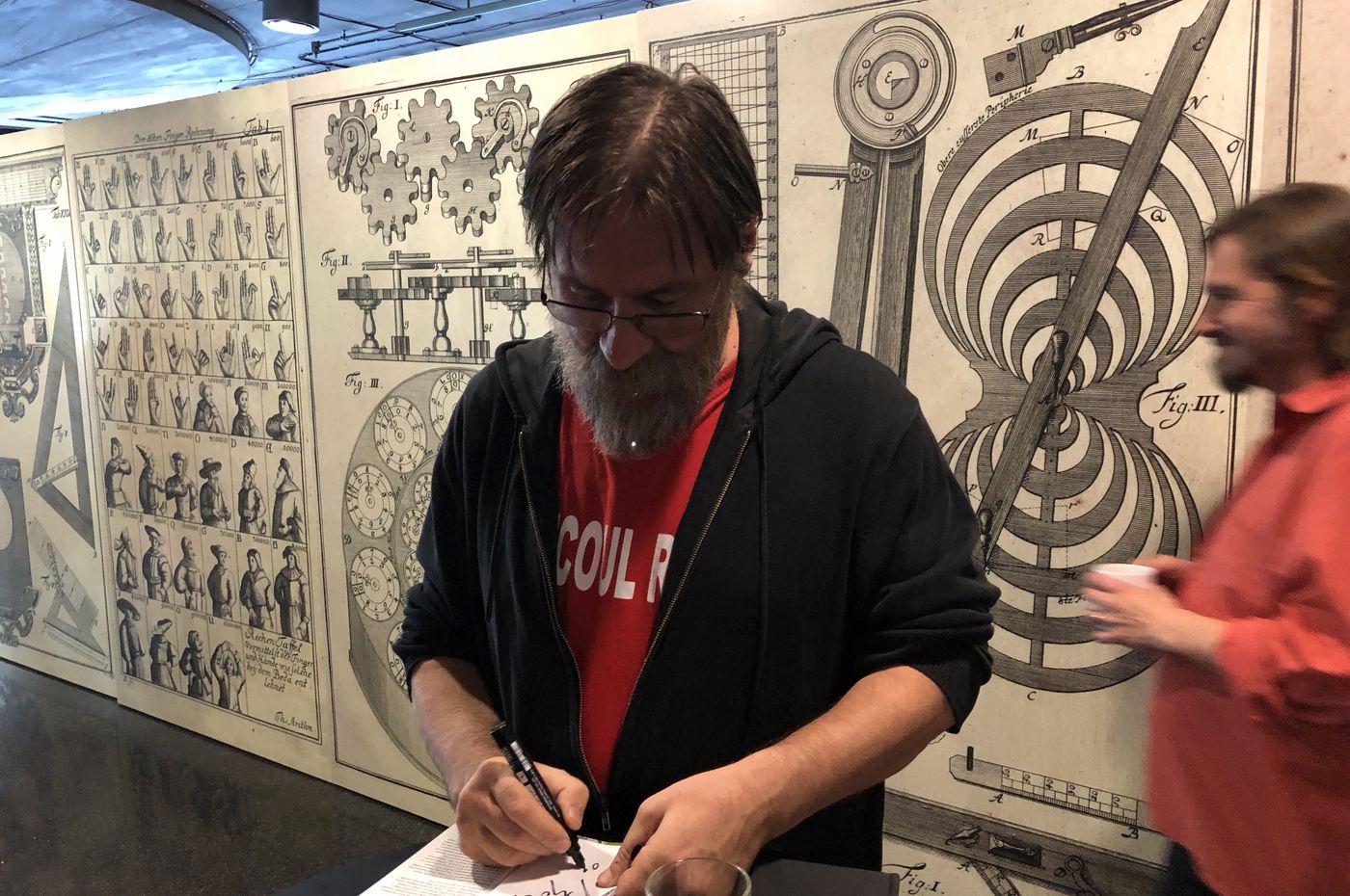 Dan Perjovschi podepisující výtisky svého skicáku